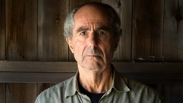 Der Author Philip Roth mit Halbglatze, grauem Hemd, steht vor einer Holzwand.