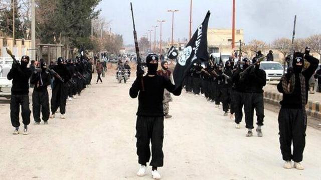 Bewaffnete Mitglieder des IS ziehen in schwarzen Kleidern und vermummt durch die Strasse.