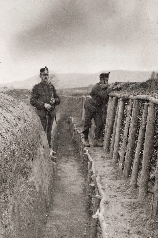 Zwei Soldaten stehen in einem Infanteriegraben. Einer zielt mit einer Waffe.