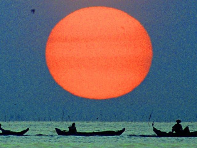 Fischerboote auf See, dahinter riesige Abendsonne