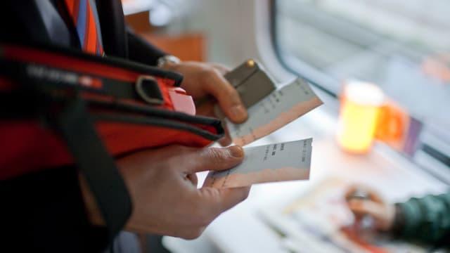 Ein Zugbegleiter kontrolliert das Zugbillet.