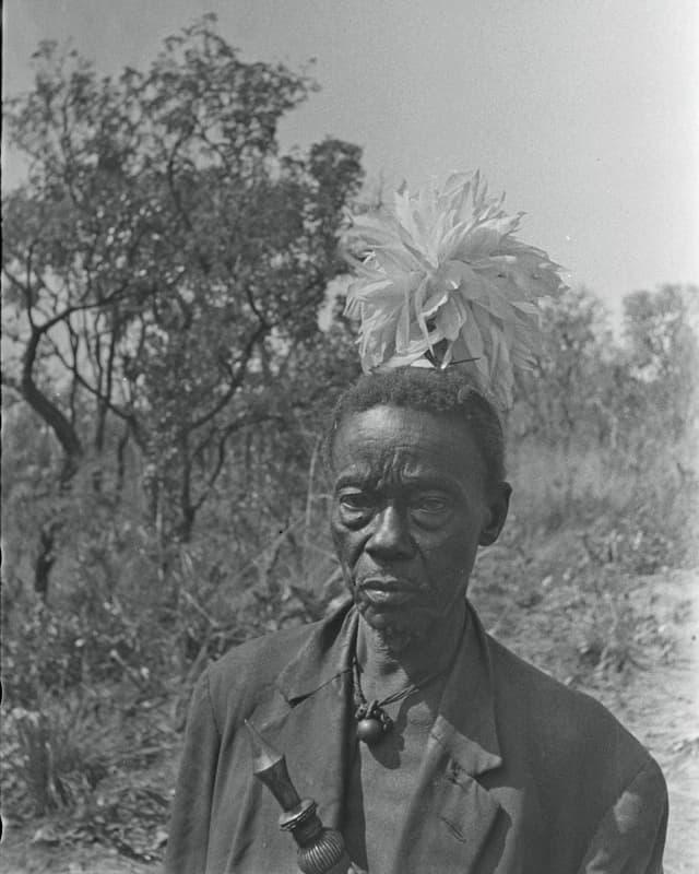 Ein schwarzer Mann mit Federschmuck.