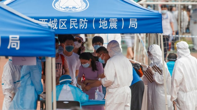 Menschen stehen in einer Schlange vor einem blauen Zelt, dort medizinische Hilfskräfte in Schutzanzügen.