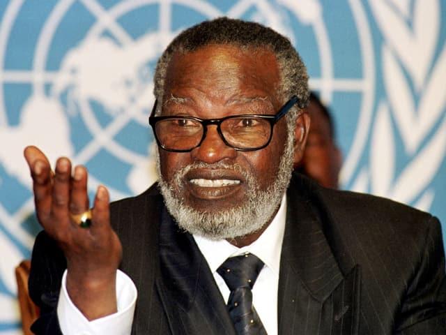 Ein afrikanischer Mann mit weissem Bart vor dem UNO-Logo.