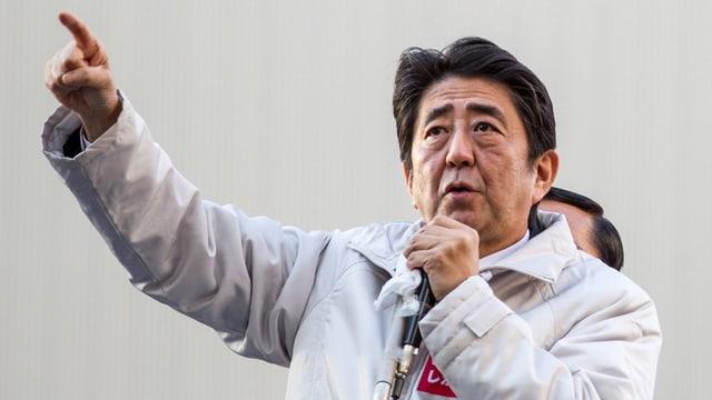 Shinzo Abe hält ein Mikrofon und hält den rechten Arm mit ausgestrecktem Zeigefinger hoch