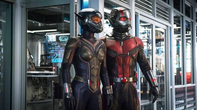 Zwei Superhelden in Anzügen stehen in einem Labor