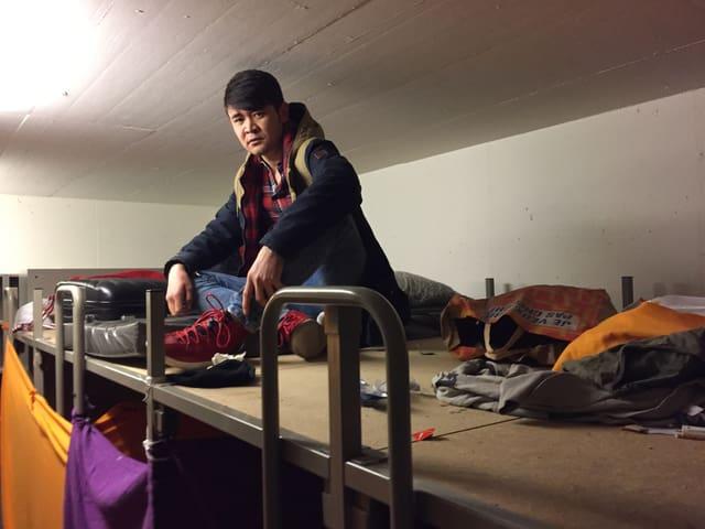 Nazari Juma Khan sitzt auf seinem Bett unter der Decke in der Asylunterkunft.