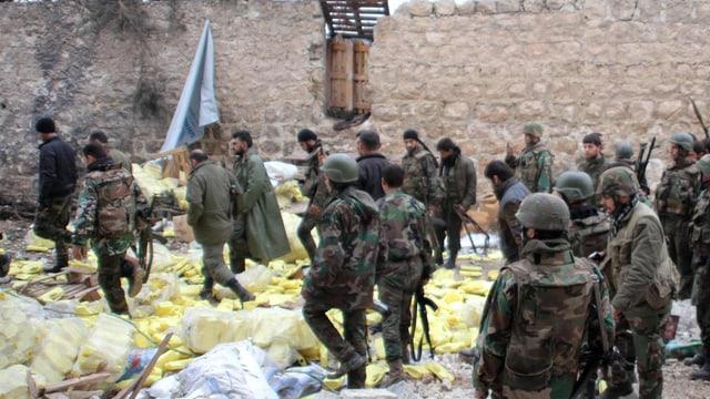 Soldatengruppe neben einer Mauer.