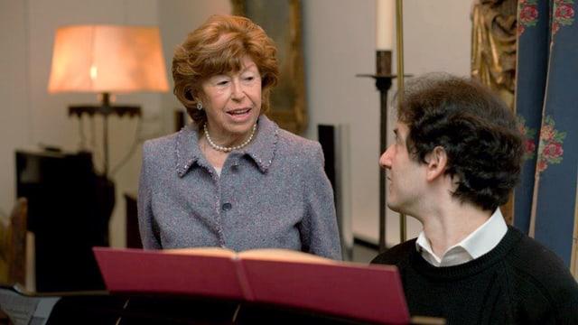 Eine ältere Frau im Gespräch mit einem Mann, der an einem Flügel sitzt.