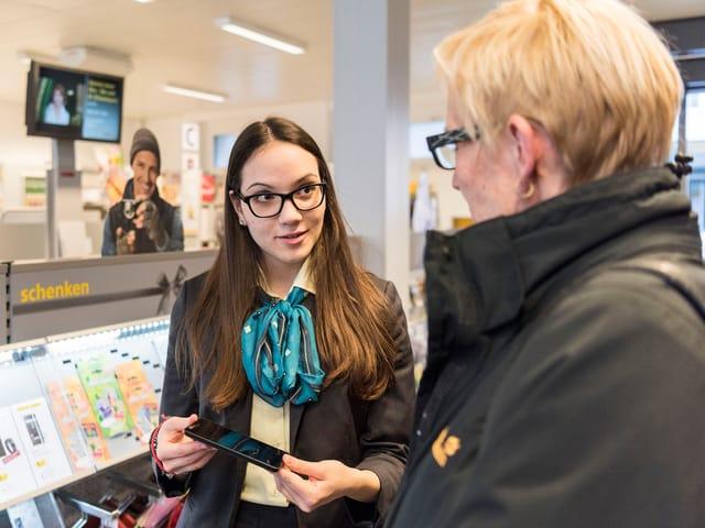 Verkaufsgespräch in einem Laden: Eine junge Frau zeigt einer Kundin ein Smartphone.