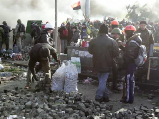 Männer sammeln Pflastersteine auf.