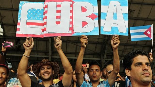 Zwei Männer mit Transparent. Darauf die US- und die kubanische Flagge und die Aufschrift «Cuba».