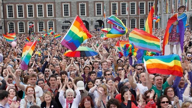 Eine Menschenmenge mit Regenbogenfahnen.