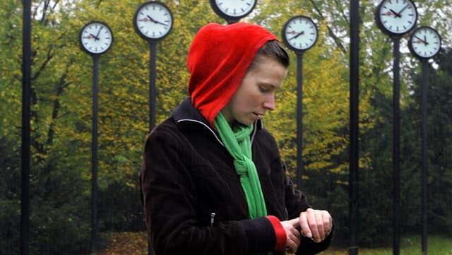 Eine Frau blickt auf die Uhr.