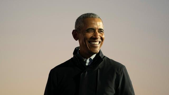 Präsident Obama trägt einen schwarzen Mantel und grinst nach rechts.