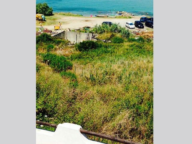 Aussicht aufs Meer, im Vordergrund eine vertrocknete Wiese und eine Baustelle.