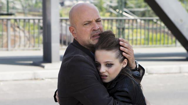 Ein kahlköpfiger Mann umarmt eine junge, stark geschminkte Frau.