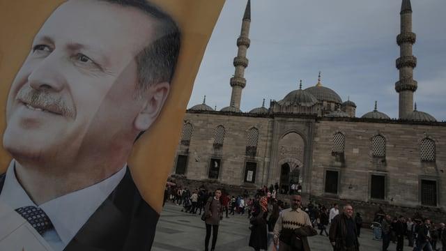 Ein Erdogan-Plakat vor einer Moschee in der Türkei, Menschen auf dem Vorplatz.
