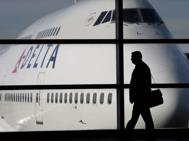 Ein Mann geht an einem Flughafen vor einer 747 durch.