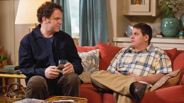 Zwei Männer führen ein Gespräch auf einem Sofa in einem Wohnzimmer.