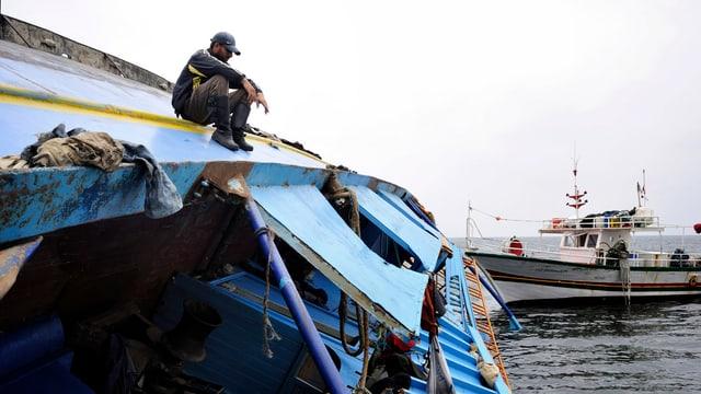 Ein Mann sitzt auf dem Bauch eines gekennterten Schiffs. Im Hintergrund ist das Schiff einer Küstenwache zu sehen.