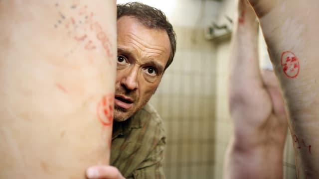 Filmszene: Brenner versteckt sich hinter einem aufgehängten, toten Schwein.