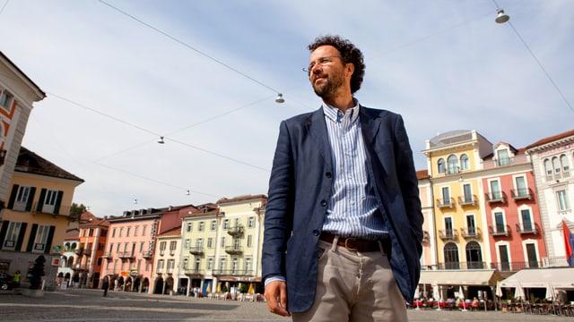 Carlo Chatrian steht auf der Piazza Grande, im Hintergrund stehen die bunten Häuser von Locarnos Altstadt.