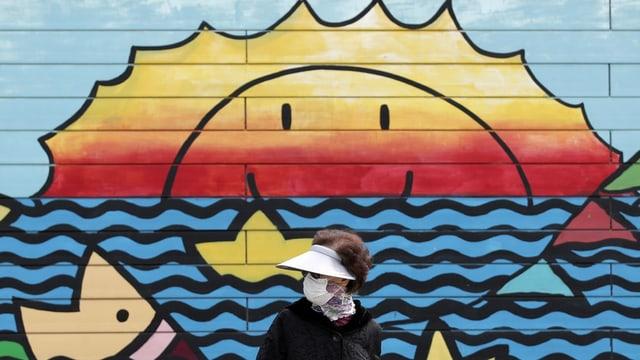 Person mit einer Schutzmaske geht an einem Wandbild vorbei.