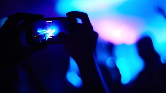 Blick auf eine blau beleuchtete Bühne. Im Vordergrund halten Hände ein Smartphone in die Höhe, mit dem jemand die Bühne fotografier.