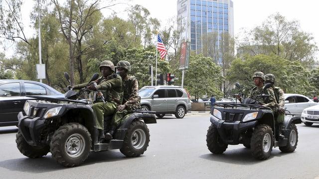 Kenianische Polizeipatrouillen zu zweit auf Quad-Fahrzeugen.