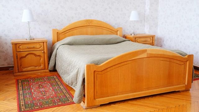 Ein Hotelbett aus Holz, mit Nachttisch und Teppich.