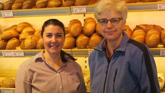 Zwei Frauen stehen vor einer Wand mit Broten.