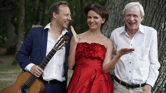 Rechts und links ein Mann, in der Mitte eine Frau. Der Mann rechts mit Gitarre in der Hand. Sie stehen vor einem Baum und strahlen.