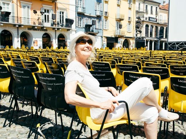 Ältere Frau mit Hut und Sonnenbrille sitzt lachend in einem gelben Plastikstuhl