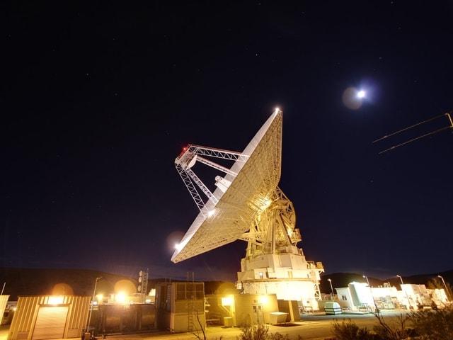 Ein riesiger beleuchteter Satellit steht auf der Erde. Es ist Nacht.
