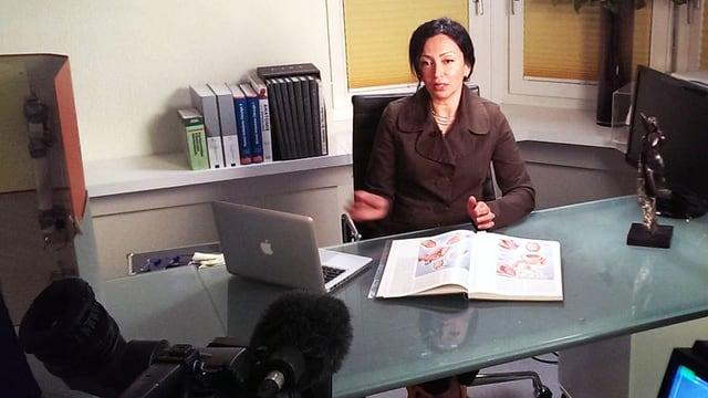 Eine Frau sitzt an einem Pult, vor sich hat sie einen Laptop und ein Buch mit medizinischen Illustrationen.