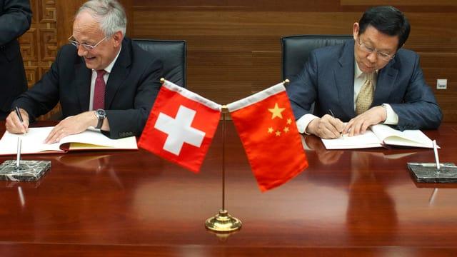 Johann Schneider-Ammann und der chinesische Handelsminister Chen Deming unterzeichnen Verträge. Im Vordergrund Schweizer und chinesische Fähnchen.