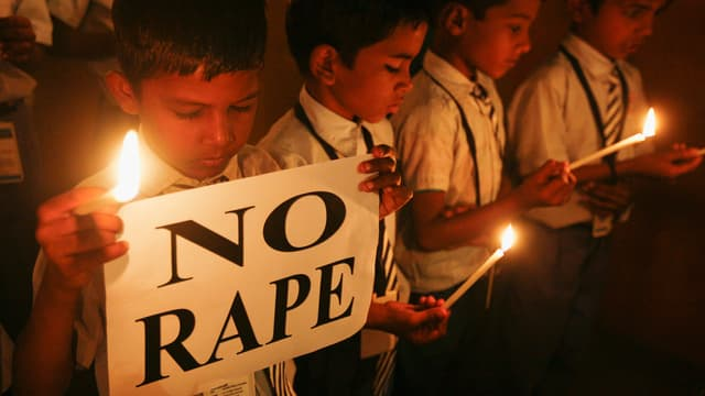Schüler mit Kerzen halten ein Transparent mit der Aufschrift «No Rape».