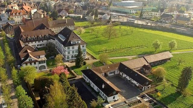 Klosteranlage mit verschiedenen Bauen auf einer grünen Wiese (Flugbild).