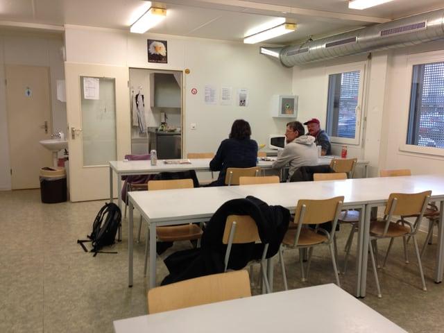 Drei Männer sitzen an einem Tisch, davor weitere Tische und Stühle.