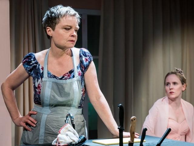 Chantal Le Moign als Rebecca, Anna-Katharina Müller als ihre Tochter, stehen an einem Tisch.