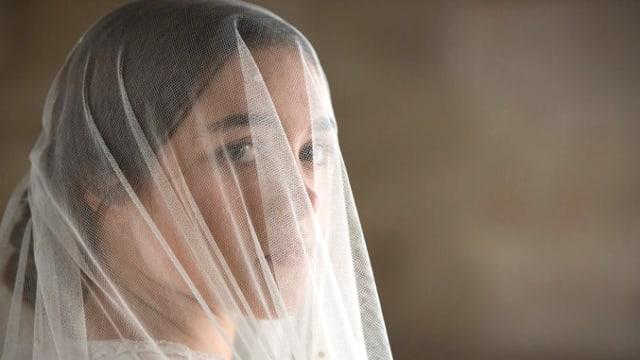 Eine junge Frau, deren Gesicht hinter einem weissen Schleier aufscheint.