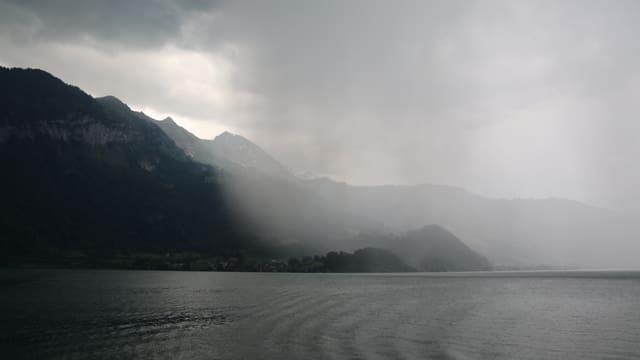 Ein Regenschauer zieht auf - graue Regenwolken über dem Thunersee.