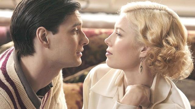 John und Larita sitzen einander gegenüber und schauen sich tief in die Augen.