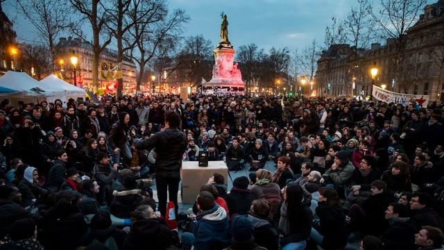 Platz voller Menschen, sitzend, Zelte links, ein Redner in der Mitte