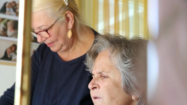 Im Vordergrund ist eine alte Frau zu sehen, also die Klientin, im Hintergrund die Pflegekraft aus Osteuropa