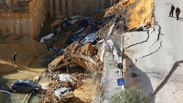Eine abgebrochene Strasse und ein überflutetes Loch, in dem kreuz und quer Autos liegen.