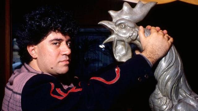 Pedo Almodóvar posiert mit einer Hahnen-Statue.