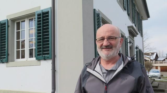 Ein Mann mit Brille, Glatze und weissem Bart steht vor einem Haus