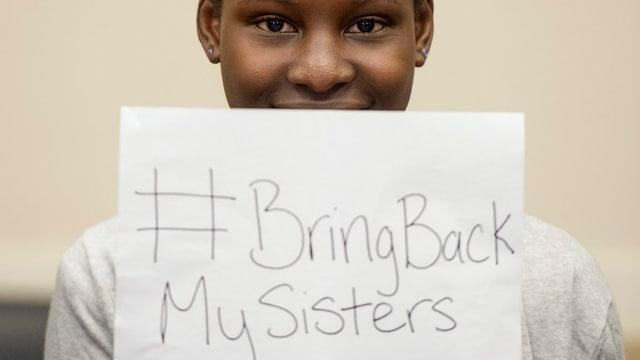 Mädchen hält Schild mit Aufschrift «Bring back my sisters».